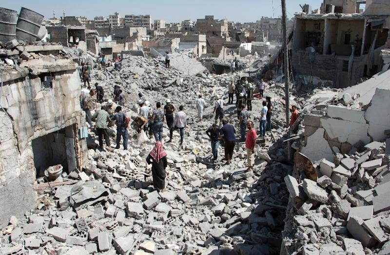 Syrians stand on the rubble of buildings after a missile fired by Syrian government forces hit a residential area in Aleppo on July 21, 2015 (AFP Photo/Karam Al-Masri)