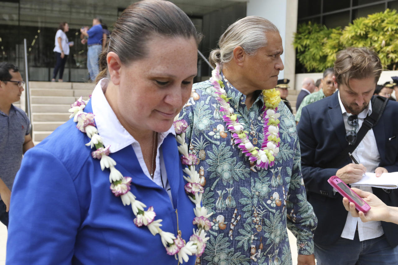 Former Honolulu Police Chief Louis Kealoha, center, and his wife, Katherine Keahola, left, leave federal court in Honolulu, Friday, Oct. 20, 2017. Kealoha and his wife, a city prosecutor, have pleaded not guilty to federal corruption charges. U.S. Magistrate Judge Richard Puglisi on Friday released Louis and Katherine Keahola on $100,000 bond each. They entered the pleas Friday after a federal grand jury indicted both of them in a public corruption case. Authorities claim the couple used their positions to bilk clients and relatives out of hundreds of thousands of dollars to fund their lavish and overextended lifestyle and then used their power to target anyone who threatened them. (AP Photo/Caleb Jones)