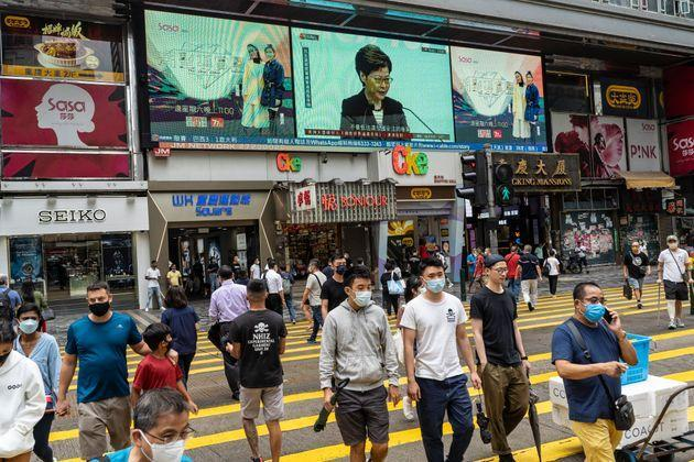 HONG KONG, CHINA - 2021/06/22: Pedestrians wearing facemasks as a precaution against the spread of covid-19 walk past a screen reporting the weekly press conference of Carrie Lam, Hong Kong's chief executive, in Tsim Sha Tsui district. Lam said that foreign governments are beautifying acts that endanger national security in their criticisms of the police crackdown on pro-democracy newspaper Apple Daily, days after five were arrested and assets linked to the newspaper frozen. (Photo by Chan Long Hei/SOPA Images/LightRocket via Getty Images) (Photo: SOPA Images via Getty Images)