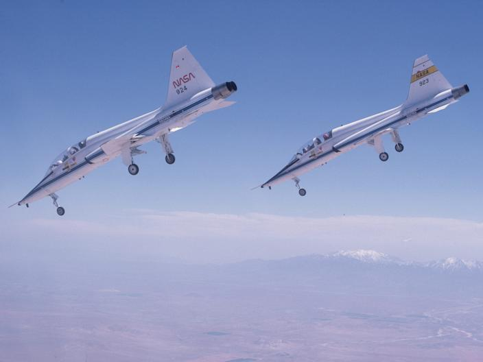 A pair of T-38s dive toward a runway at Edwards Air Force Base in Calif.