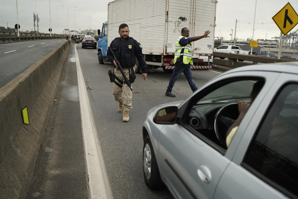 Federal Highway Police officer walks with his weapon as he indicates the way back to the drivers at a blocked access for the bridge connecting the city of Niteroi to Rio de Janeiro , Brazil, Tuesday, Aug. 20, 2019 during a hostage standoff. An armed man holding dozens of people hostage on a public bus and threatening to set the vehicle on fire was seized by police after a four-hour long standoff, Brazilian police said.  (AP Photo/Leo Correa)