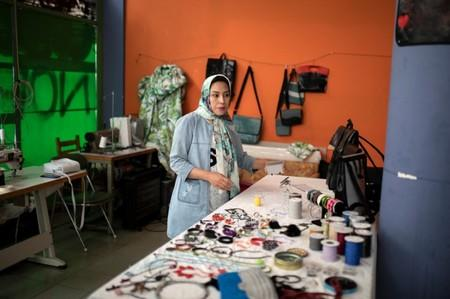 Afghan refugee and designer-maker Fariba Amini, 31, stands in front of her creations in a studio in Athens