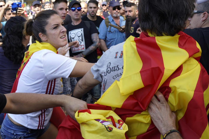 A woman wearing a Spanish flag hits a man wearing an Independence flag, followinga demonstration erupting in clashes in Barcelona, Spain, on Saturday, Sept. 29, 2018. Catalan separatists clashed with police on Saturday in downtown Barcelona as tensions increase before the anniversary of the Spanish region's illegal referendum on secession that ended in violent raids by security forces. (AP Photo/Daniel Cole)