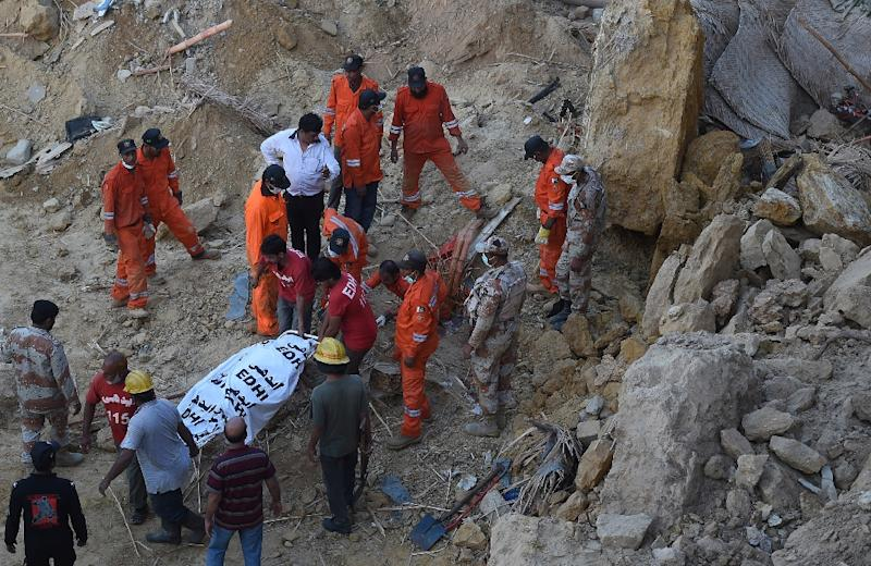 Rescuers carry the body of a victim of a landslide in Karachi, on October 13, 2015 (AFP Photo/Asif Hassan)