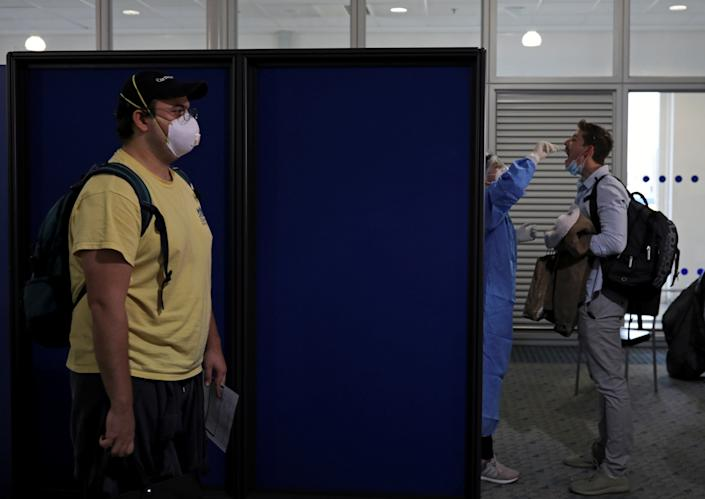 A passenger from the first Lufthansa flight to Greece, following a nationwide lockdown against the spread of the coronavirus disease (COVID-19), is tested for coronavirus, upon their arrival at the Eleftherios Venizelos International Airport in Athens, Greece, May 18, 2020. REUTERS/Alkis Konstantinidis     TPX IMAGES OF THE DAY