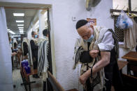 """Holocaust survivor Yehoshua Datsinger places tefillin on his arm above the Auschwitz concentration camp identification number tattoo, during morning prayer at a synagogue limited to 20 people during lockdown, in Bnei Brak, Israel, Monday, Sept. 21, 2020. Photographer Oded Balilty said he was struck that even though older people were the most vulnerable to the coronavirus, Datsinger still went to synagogue every morning to pray. """"He survived this latest war as well,"""" Balilty said. (AP Photo/Oded Balilty)"""