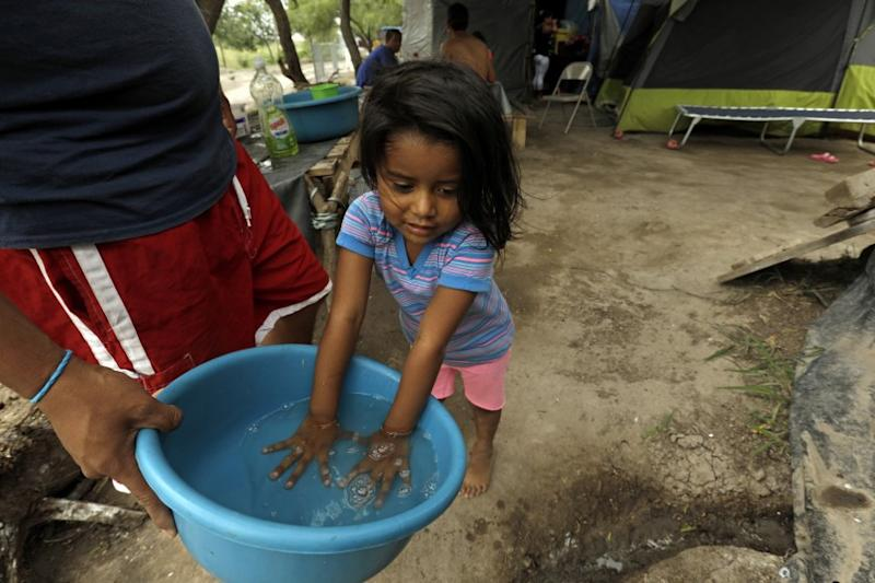 """MATAMOROS, MEXICO-MAY 15, 2020-Three-year-old Angie Garcia, originally from El Salvador, washes her hands in a bucket before eating lunch. Her family are asylum seekers living in a refugee camp in Matamoros, Mexico. Hundreds of asylum seekers are waiting under the """"Remain in Mexico"""" program in the camp, where there has yet to be one case of Covid-19 during the pandemic. Sanitation conditions have greatly improved in the camp in the past six months. (Carolyn Cole/Los Angeles Times)"""