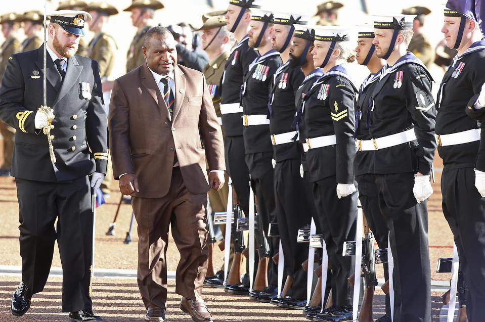 Papua New Guinea's Prime Minister James Marape, second from left, inspects troops as he is officially welcomed to Australia's Parliament House in Canberra Monday, July 22, 2019. Marape says his country's relationship with China in not open to discussion during his current visit to Australia. (AP Photograph/Rod McGuirk)