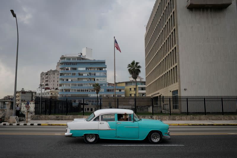 A vintage car passes by the U.S. Embassy in Havana