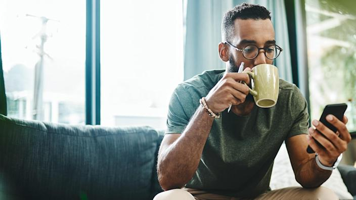 Shot of a young man using a smartphone and having coffee on the sofa at home.