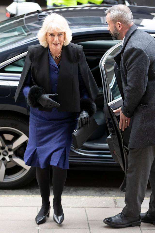 "<p>Camilla bundled up for her visit to the Royal Academy of Arts wearing a cape jacket by <a rel=""nofollow"" href=""https://orchardmile.com/amanda-wakeley/midtown-black-tailored-cape-awk920795ad?color=black&gclid=Cj0KCQiA1sriBRD-ARIsABYdwwHzurlsA3t5ujGo1YJ3M0Z3sNsTvrREIHzyfcJS-Nud-m0mGatlLPUaAmkVEALw_wcB&glcountry=US"">Amanda Wakeley</a> over her blue suit. </p><p><a rel=""nofollow"" href=""https://orchardmile.com/amanda-wakeley/midtown-black-tailored-cape-awk920795ad?color=black&gclid=Cj0KCQiA1sriBRD-ARIsABYdwwHzurlsA3t5ujGo1YJ3M0Z3sNsTvrREIHzyfcJS-Nud-m0mGatlLPUaAmkVEALw_wcB&glcountry=US"">SHOP SIMILAR</a> <em>Midtown Black Tailored Cape, Amanda Wakeley, $585 </em></p>"