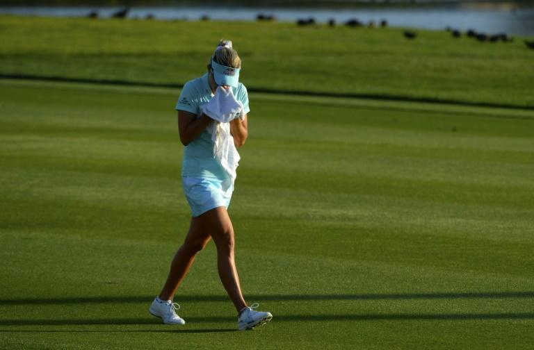 Lexi Thompson cries in a towel as she walks to the 18th green after her second shot during the final round of the ANA Inspiration on the Dinah Shore Tournament Course on April 2, 2017 in California
