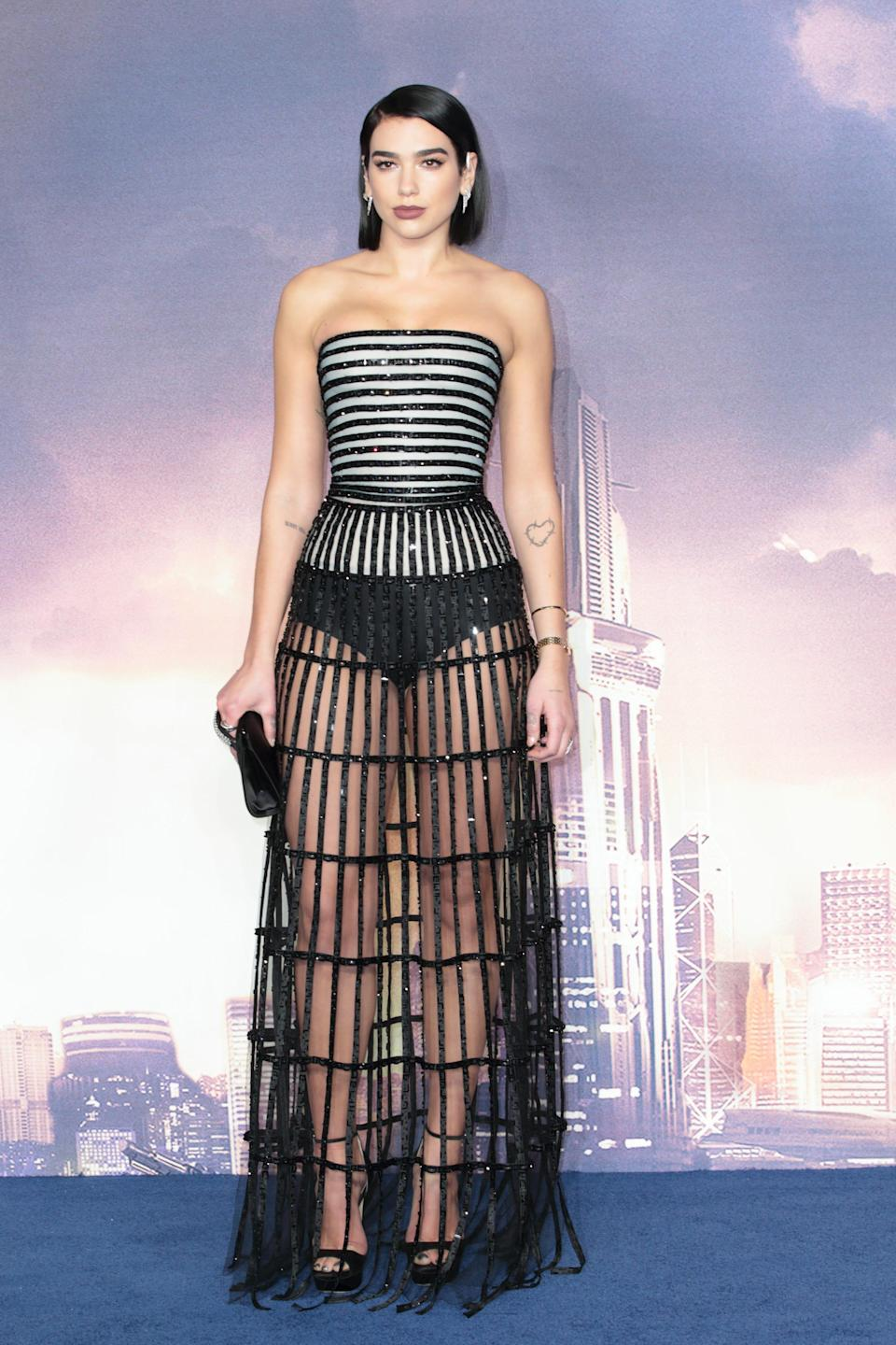 Dua Lipa stands in a black and white dress in front of a sky backdrop.