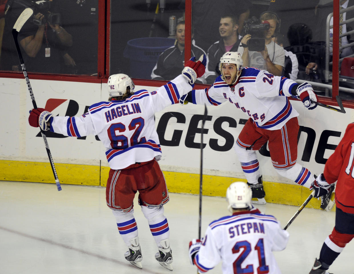 New York Rangers right wing Ryan Callahan (24) celebrates his goal with teammates Carl Hagelin (62) and Derek Stepan (21) against the Washington Capitals during the third period of Game 7 first-round NHL Stanley Cup playoff hockey series, Monday, May 13, 2013, in Washington. The Rangers won 5-0. (AP Photo/Nick Wass)