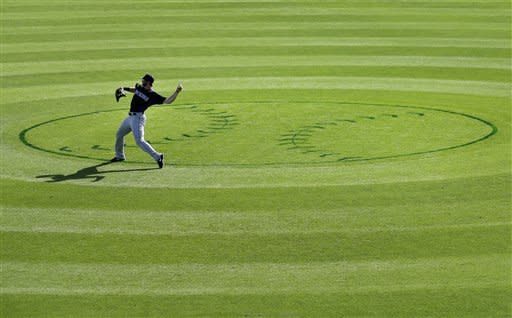 Colorado Rockies left fielder Charlie Blackmon warms up before starting the bottom of the ninth inning against the Kansas City Royals in a spring training baseball game Tuesday, March 19, 2013, in Surprise, Ariz. (AP Photo/Gregory Bull)