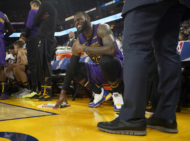 LeBron James was in pain on the bench Tuesday night against the Warriors. (AP)