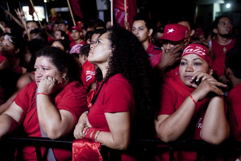 Supporters of the Salvador Sanchez Ceren, presidential candidate, current vice president for the ruling Farabundo Marti National Liberation Front (FMLN) listen to results of the presidential elections during a demonstration in San Salvador, El Salvador, Sunday, Feb. 2, 2014. El Salvador's electoral tribunal said late Sunday that with about 58 per cent of the votes counted, Vice-President Salvador Sanchez had 49 per cent in his bid to extend the rule of the Farabundo Marti National Liberation Front, the party of former civil war guerrillas that won the presidency for the first time in 2009. Sanchez was just under the 50 per cent plus one vote he needed to win outright, but election tribunal chief Eugenio Chicas predicted the candidate would fall short and have to face a runoff. San Salvador Mayor Norman Quijano was second with nearly 39 per cent as the candidate of the long-governing conservative Nationalist Republican Alliance, known as ARENA. (AP Photo/Esteban Felix)