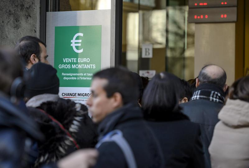People queue at a bureau de change in Geneva on January 15, 2015, after Switzerland's central bank scrapped a policy to artificially hold down the value of the Swiss franc against the euro