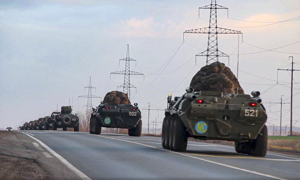 This photo made from the footage provided by Russian Defense Ministry press service on in Tuesday, Nov. 10, 2020 shows Russian military vehicles carry peacekeepers on their way to an airport in unknown place in Russia. Scores of Russian peacekeepers were heading to Nagorno-Karabakh on Tuesday morning, hours after Armenia and Azerbaijan agreed to halt the fighting over the separatist region in a pact signed with Moscow which envisions the deployment of nearly 2,000 Russian peacekeepers and territorial concessions. (Russian Defense Ministry Press Service via AP)