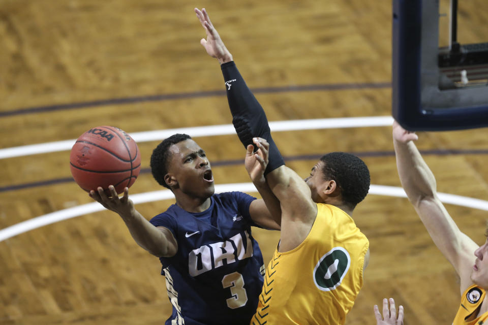 Oral Roberts guard Max Abmas (3) goes up for a layup against North Dakota State defender Dezmond McKinney (0) dduring an NCAA college basketball game for the Summit League men's tournament championship Tuesday, March 9, 2021, in Sioux Falls, S.D. (AP Photo/Josh Jurgens)