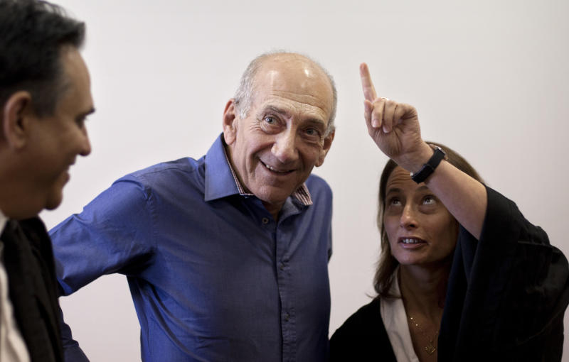 Former Israeli Prime Minister Ehud Olmert, center, speaks with his attorneys as he attends the sentence hearing in a corruption case, at Jerusalem's District Court, Monday, Sept. 24, 2012. Olmert cleared a major hurdle toward a possible return to politics on Monday, receiving an unexpectedly light sentence for his role in a corruption case that forced him from office. (AP Photo/Sebastian Scheiner, Pool)