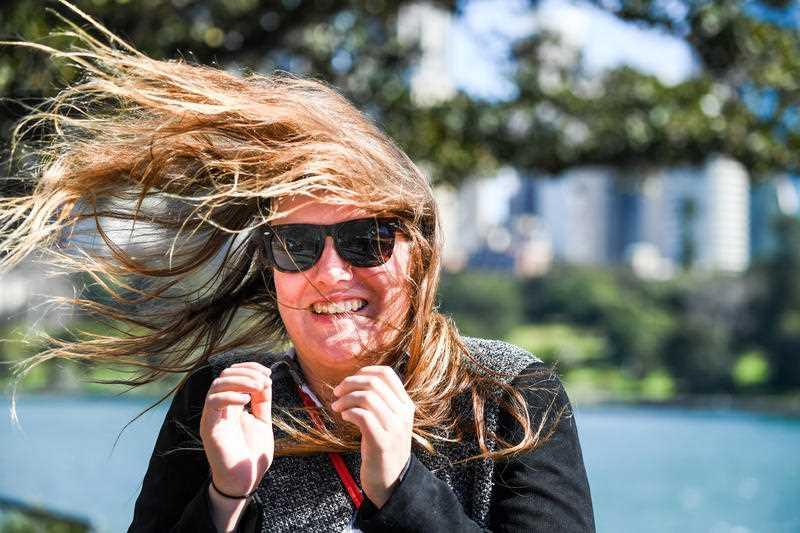 A tourist is buffeted by winds at Mrs Macquaries Road, Botanic Gardens, Sydney.