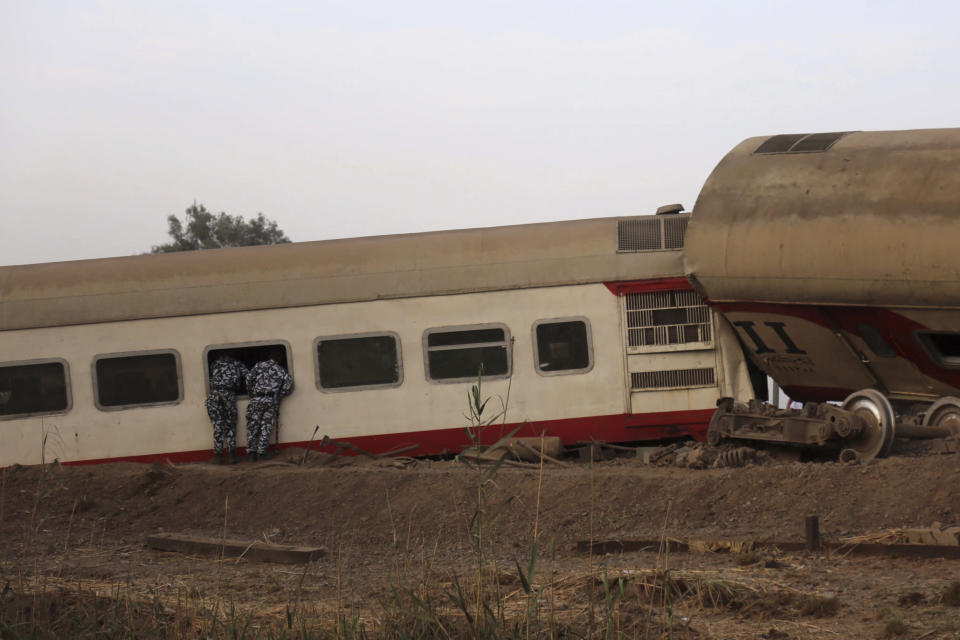 Security forces look inside a passenger train that derailed injuring some 100 people, near Banha, Qalyubia province, Egypt, Sunday, April 18, 2021. At least eight train wagons ran off the railway, the provincial governor's office said in a statement. (AP Photo/Fadel Dawood)