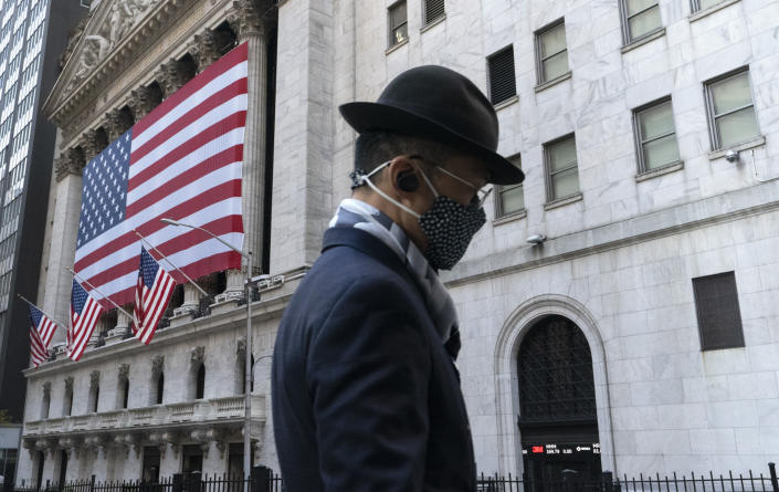 FILE - In this Nov. 16, 2020 file photo a man wearing a mask passes the New York Stock Exchange in New York. Stocks are opening lower on Wall Street again as Apple and other Big Tech companies give up more ground. The S&P 500 index fell 1.2% in the early going Tuesday, May 11, 2021. (AP Photo/Mark Lennihan, File)