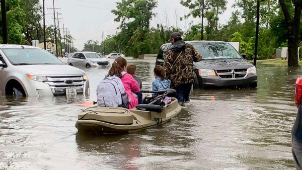 PHOTO: Parents use boats to pick up students from schools after nearly a foot of rain fell in Lake Charles, La., May 17, 2021.  (Rick Hickman/American Press via AP)