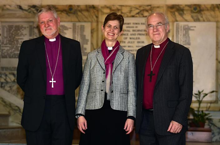 Reverend Libby Lane poses for pictures with Bishop of Birkenhead Keith Sinclair (L) and Bishop of Chester Peter Forster (R) in Stockport, northwest England, on December 17, 2014 (AFP Photo/Paul Ellis)