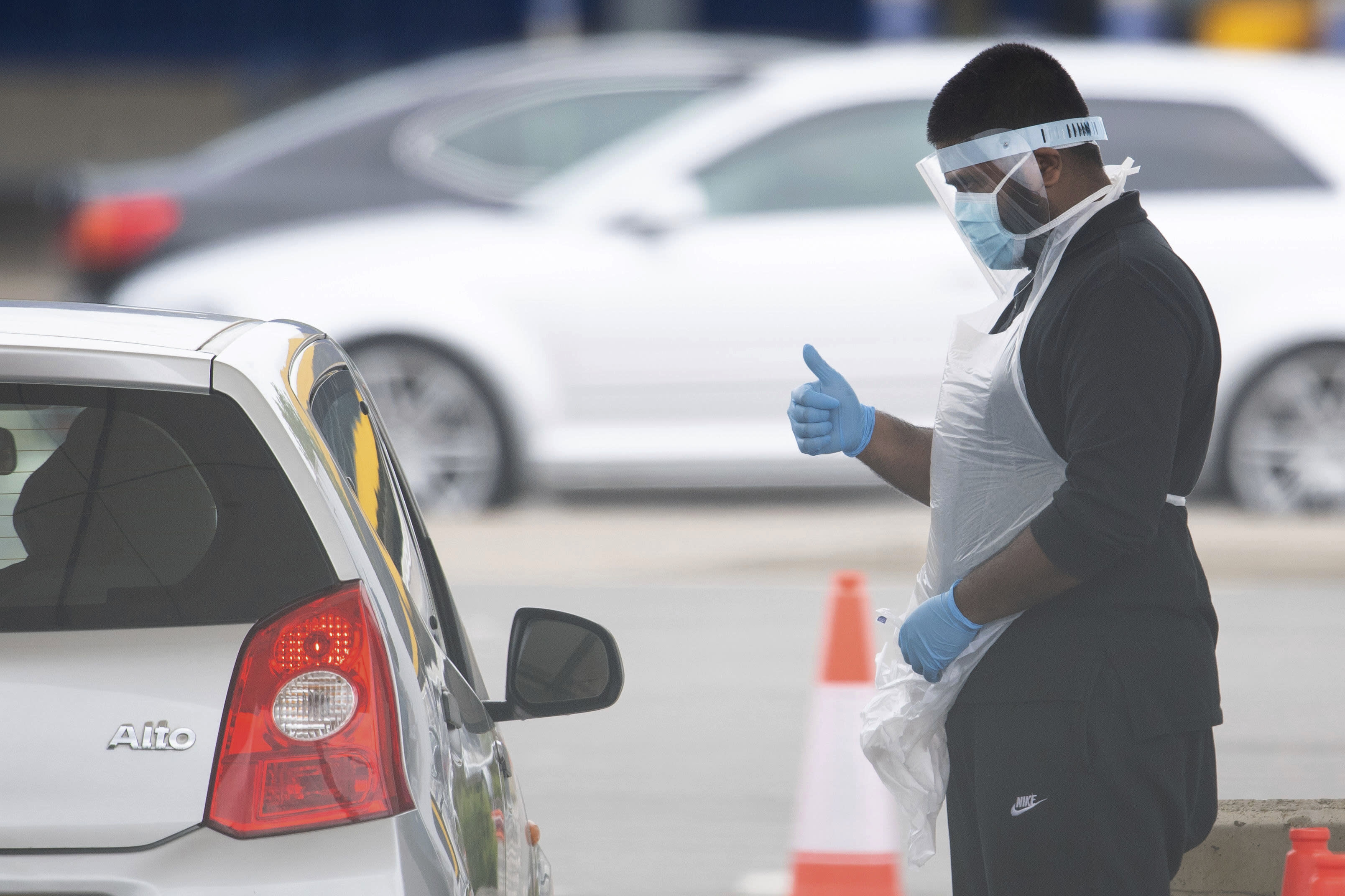 A tester, wearing a mask to protect against coronavirus, gestures to a driver at a drive through coronavirus testing site at IKEA in Wembley, north London, Thursday April 30, 2020. (Dominic Lipinski/PA via AP)