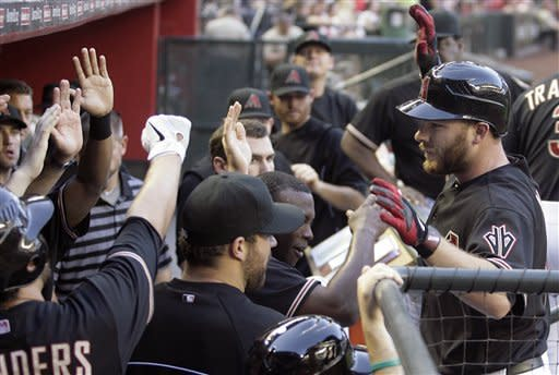 Arizona Diamondbacks' Jason Kubel, right, is congratulated by teammates as he returns to the dugout after hitting a solo home run off Atlanta Braves pitcher Tommy Hanson in the second inning of a baseball game on Saturday, April 21, 2012, in Phoenix. (AP Photo/Paul Connors)