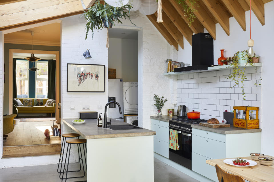A kitchen extension with exposed beams, light blue units and plants that hang from the ceiling
