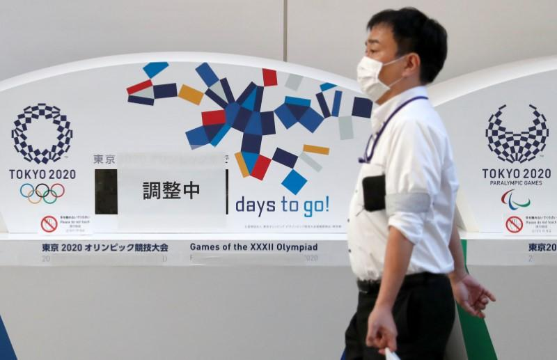A man wearing a protective face mask due to the outbreak of coronavirus disease (COVID 19) walks past countdown clocks for the opening of Tokyo 2020 Olympic and Paralympic Games in Tokyo