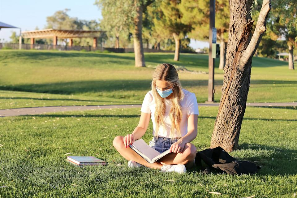 A student wearing a face mask is studying outside, practicing social distancing.