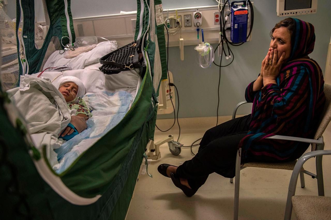 <p>Malalai Rafi watches over her son Omar, 8, in the recovery room at UC Davis Children's Hospital after his cranioplasty surgery on Aug.13, 2015. Surgeons put a piece of his skull back into place, which was removed in a previous procedure due to brain swelling. The operation wasn't successful; Omar's skull would not be repaired until nearly nine months later, in May 2016. Omar who suffered brain damage from the accident and his father were bicycling along Edison Avenue in Sacramento, Calif., when they were both hit by a car. Omar's father Mustafa Rafi, an Afghan SIV who had recently moved his family to the U.S. twenty days earlier, was killed in the accident leaving Malalai who spoke no english and couldn't drive to care for her four children. (Photograph by Renée C. Byer/The Sacramento Bee) </p>