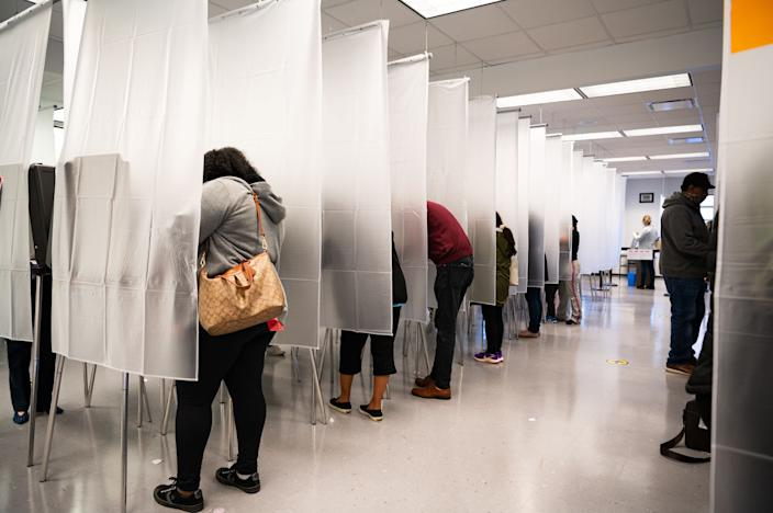 Residents of Cuyahoga county, separated by plastic due to health concerns amid the coronavirus pandemic, fill out paper ballots for early, in-person voting at the board of elections office in downtown Cleveland, Ohio, on Oct. 16, 2020.