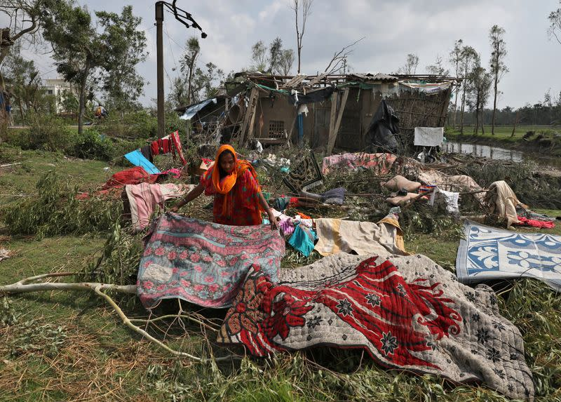 A woman spreads quilts and sheets for drying after salvaging them from the rubble of her damaged house in the aftermath of Cyclone Amphan, in South 24 Parganas district