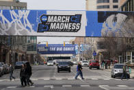 March Madness banners for the NCAA college basketball tournament cover crosswalks in downtown Indianapolis, Wednesday, March 17, 2021. (AP Photo/Darron Cummings)