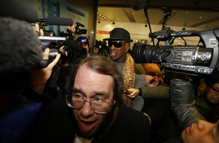 Former NBA basketball player Dennis Rodman is surrounded by the media as he returns from his trip to North Korea at Beijing airport, December 23, 2013. REUTERS/Jason Lee