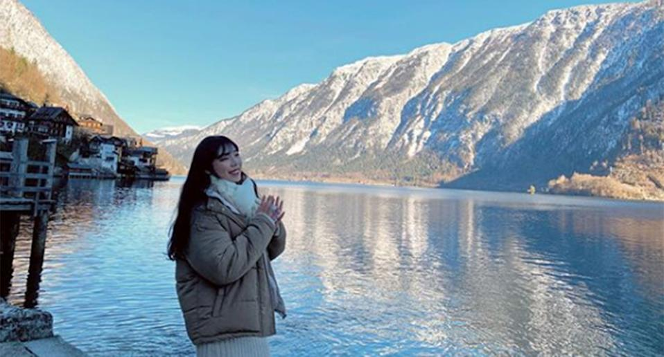 A woman poses for a photo at the Hallstatt waterfront with the mountains behind her.