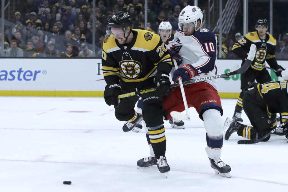 Boston Bruins center Joakim Nordstrom (20) and Columbus Blue Jackets center Alexander Wennberg (10) compete for the puck in the second period of an NHL hockey game, Thursday, Jan. 2, 2020, in Boston. (AP Photo/Elise Amendola)