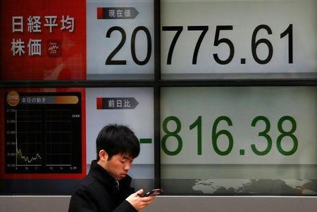 A man looks at a mobile phone in front of an electronic board showing Japan's Nikkei average outside a brokerage in Tokyo, Japan, March 23, 2018. REUTERS/Toru Hanai