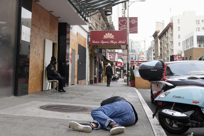 A man lies on the street as a security guard sits in front of the entrance to the Hotel Diva in San Francisco, Saturday, Nov. 21, 2020. Some counties in California are pushing ahead with plans to wind down a program that's housed homeless people in hotel rooms amid the pandemic, despite an emergency cash infusion from the state aimed at preventing those same residents from returning to the streets in cold, rainy weather as the virus surges. (AP Photo/Jeff Chiu)