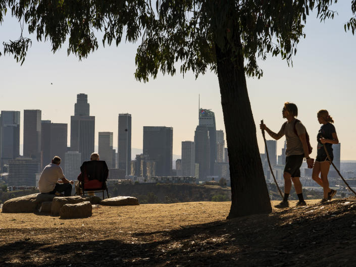 FILE - In this Monday, Jan. 11, 2021, file photo, Albert Maghbouleh, left, and Miles Santamour, 89, with Amigos de Jaibalito Foundation (ADJ) share lunch outdoors overlooking the skyline of Los Angeles. As the U.S. goes through the most lethal phase of the coronavirus outbreak yet, governors and local officials in hard-hit parts of the country are showing little willingness to impose any new restrictions on businesses to stop the spread. (AP Photo/Damian Dovarganes, File)