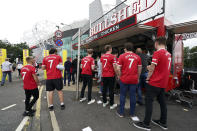Fans wearing Manchester United's Cristiano Ronaldo shirts queue at a food stand outside the stadium before the English Premier League soccer match between Manchester United and Newcastle United at Old Trafford stadium in Manchester, England, Saturday, Sept. 11, 2021. (AP Photo/Jon Super)