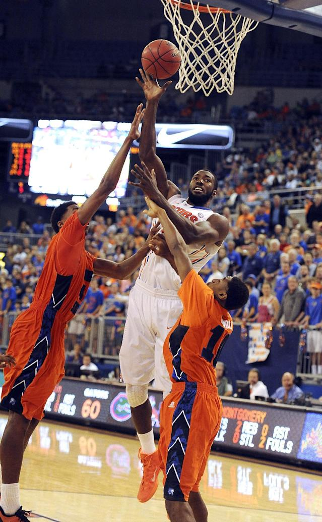 Florida center Patric Young (4) goes to the basket with Savannah State forward Jyles Smith (44) and guard Alante Fenner (1) trying to block the shot which would have put Young over the 1,000 career point mark during the second half of an NCAA college basketball in Gainesville, Fla., Sunday, Dec. 29, 2013. Florida won the game 76-34. (AP Photo/Phil Sandlin)