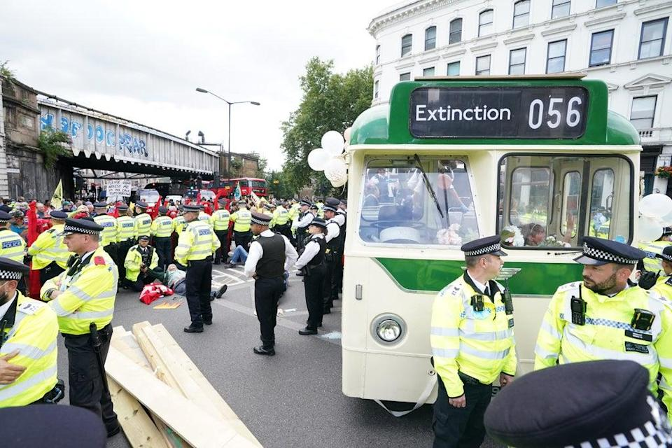 Police and demonstrators with a bus parked on London Bridge (Ian West/PA) (PA Wire)