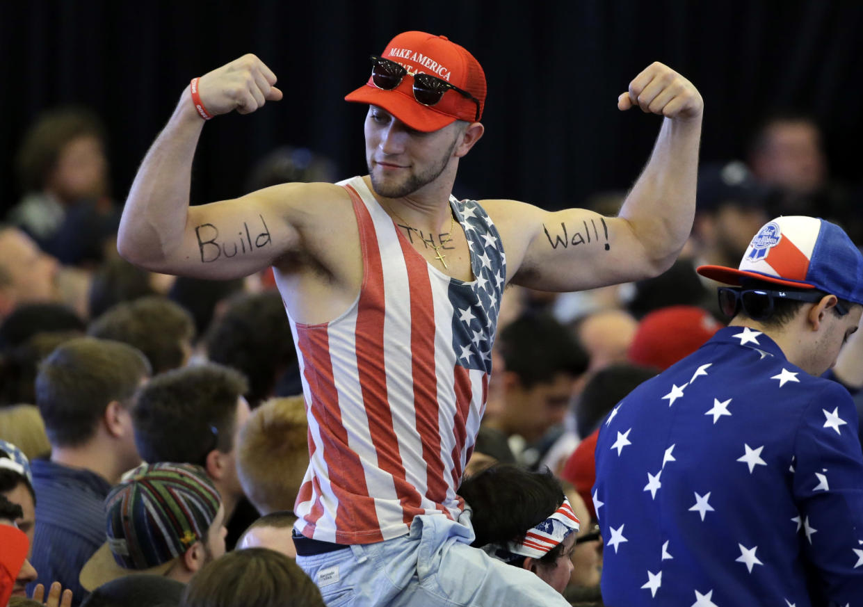 """A Donald Trump supporter flexes his muscles with the words """"Build the Wall"""" written on them as Republican presidential candidate Donald Trump speaks at a campaign rally on April 15, 2016, in Plattsburgh, N.Y. (Photo: Elise Amendola/AP)"""