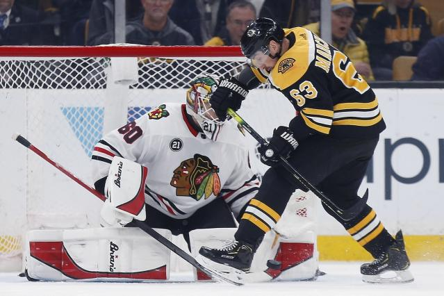 Boston Bruins' Brad Marchand (63) tries to get a shot on Chicago Blackhawks' Collin Delia (60) during the first period of an NHL hockey game in Boston, Tuesday, Feb. 12, 2019. (AP Photo/Michael Dwyer)
